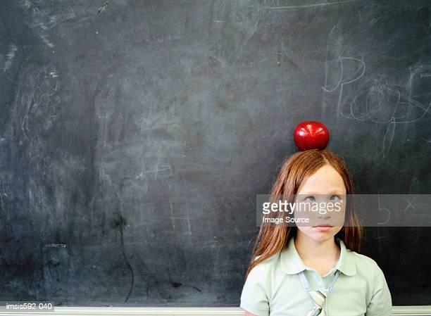 Mädchen balancing einen Apfel auf dem Kopf