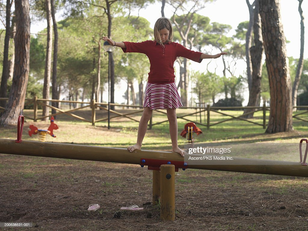 Girl (10-12) balancing atop seesaw, arms outstretched : Stock Photo
