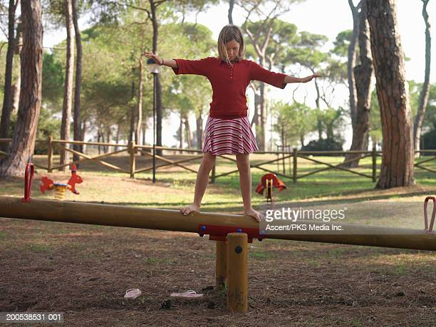 girl (10-12) balancing atop seesaw, arms outstretched - biciancola foto e immagini stock