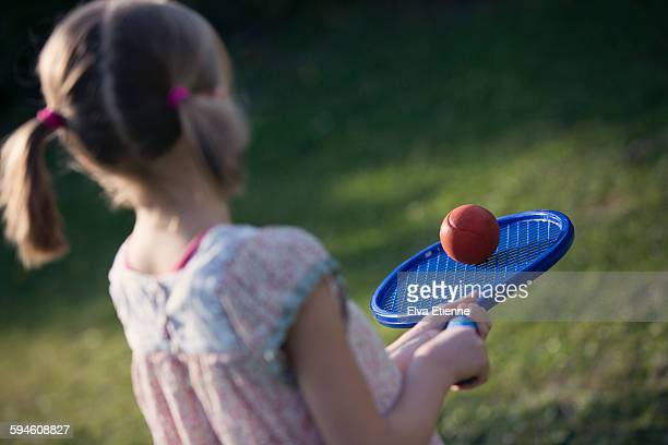 Girl balancing ball on tennis racket