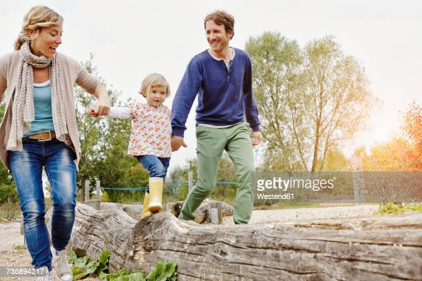 Girl balancing on a log supported by parents