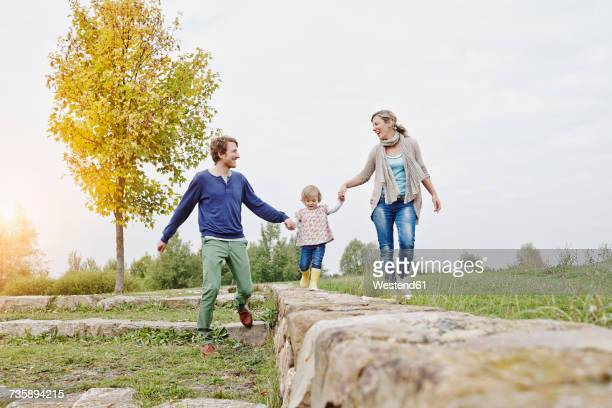 Girl balancing on a wall supported by parents