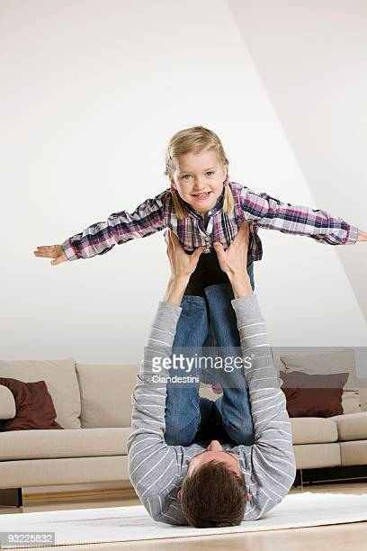 Girl (2-3) balancing on father's feet