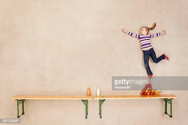 Girl balancing on pile of apples