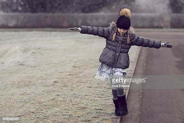 Girl balancing on roadside curb