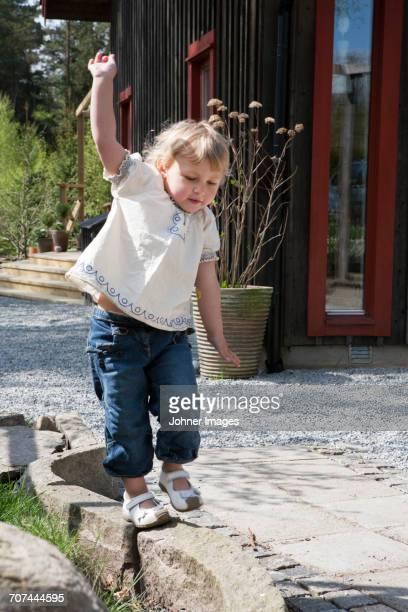 Girl balancing on small wall