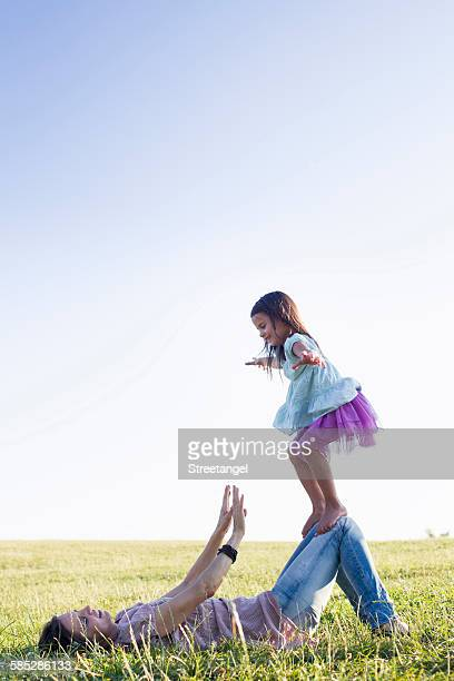 girl balancing on top of mothers knees in park - knees together stock photos and pictures