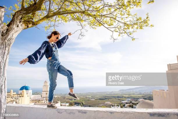Girl balancing on top of wall, Oa, Santorini, Kikladhes, Greece