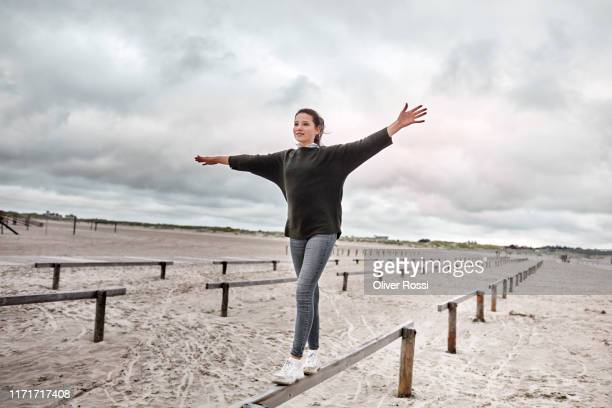 girl balancing on wooden plank on the beach - gleichgewicht stock-fotos und bilder