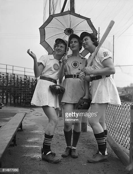Girl baseball players are shown in uniform holding an umbrella a bat and a mitt Left to right sisters Joanne Weaver 15 years old outfielder Jean...