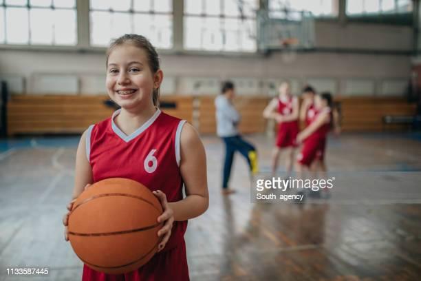mädchen basketballspieler steht vor trainer und teamkollegen - anstoß sportbegriff stock-fotos und bilder