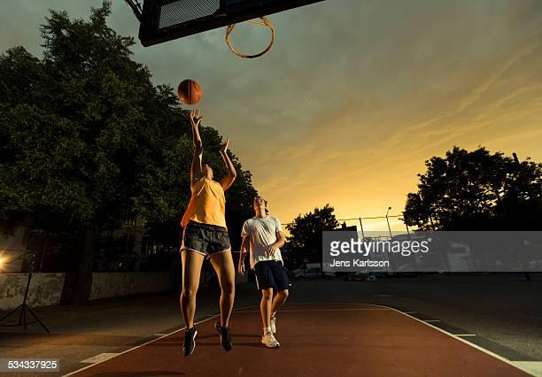Girl basketball playing against guy