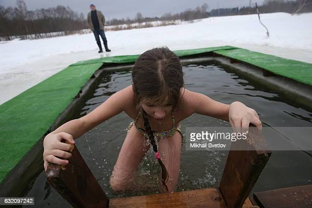 A girl bathes in the icy cold water while celebrating the Epiphany church holiday in the village Kholmy on January 19 50 km West of Moscow Russia The...