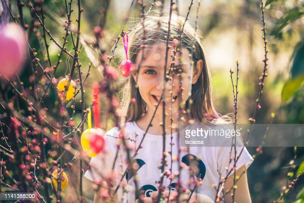 girl behind decorated easter twigs - easter flowers stock pictures, royalty-free photos & images