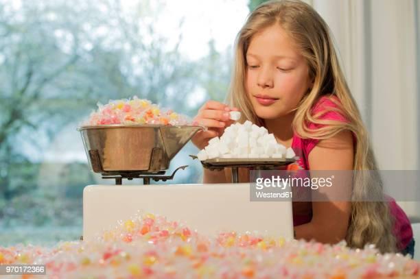 girl behind scales, weighing sugar cubes and a lot of candies - schlechte angewohnheit stock-fotos und bilder