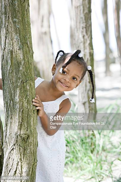 """girl (2-3) behind tree, smiling, portrait - """"compassionate eye"""" fotografías e imágenes de stock"""