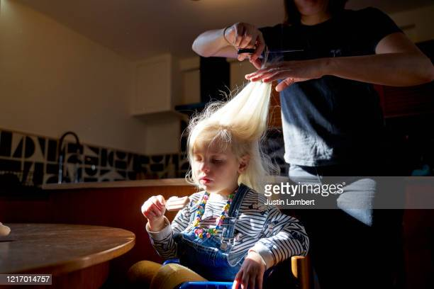 girl being bribed with ice cream to have hair cut at home by mother - mother stock pictures, royalty-free photos & images