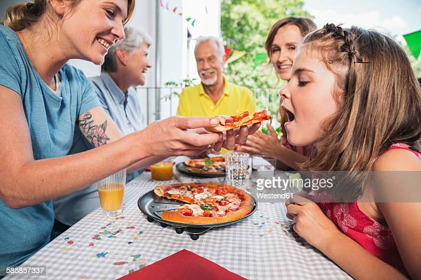 Girl being fed with homemade pizza at family party