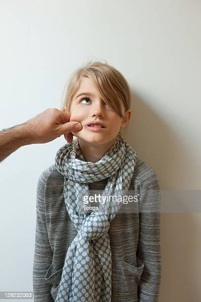 Girl being pinched on the cheek by dad