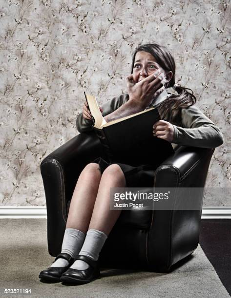 Girl (7-9) being silenced by hand emerging from book