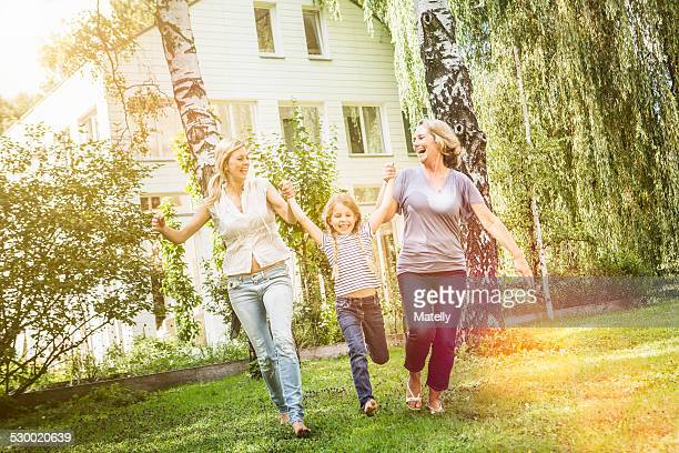 Girl being swung by mother and grandmother
