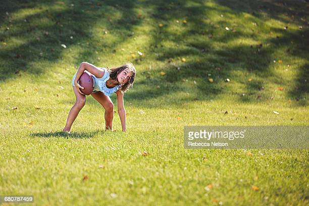 girl bending forward playing american football in park - little girls bent over stock photos and pictures