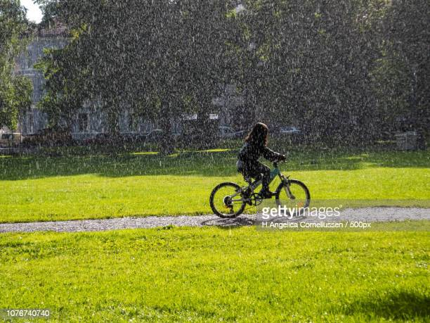 Girl bikes in urban park with rain and sunshine