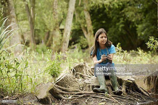 Girl birdwatching. Sitting on a tree stump holding binoculars.