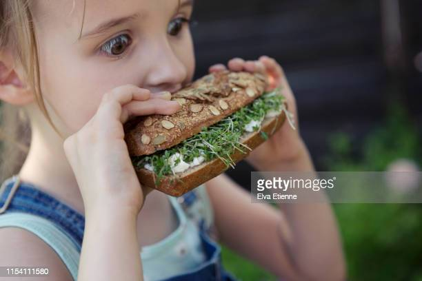 girl biting into a healthy brown bread roll stuffed with cream cheese and cress - part of a series foto e immagini stock