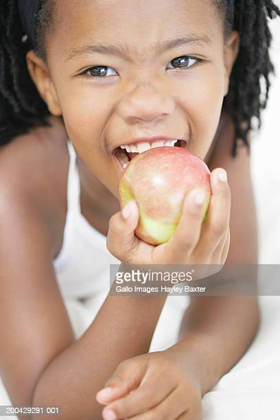 girl (5-7) biting into apple, portrait, close-up - kid girl eating apple stock photos and pictures