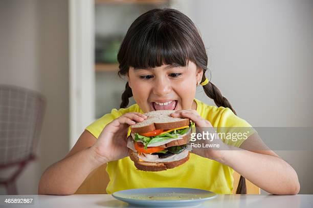 Girl biting into sandwich
