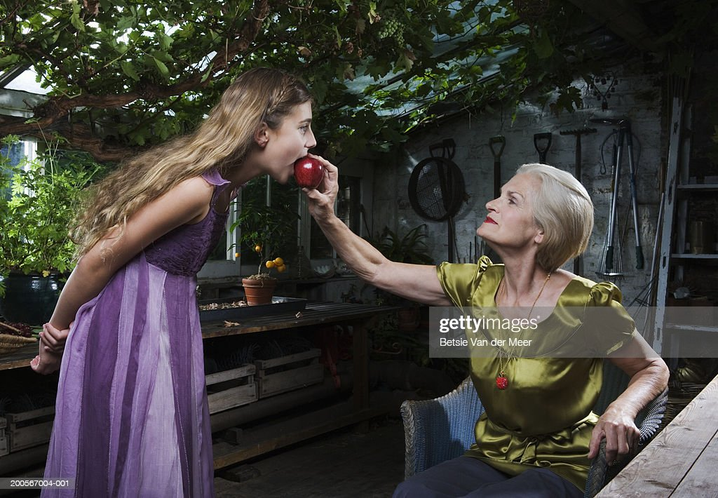 Girl (10-11) biting red apple offered by senior woman : Stock Photo
