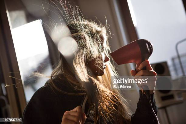 girl (12-13) blow drying her long hair with an electric hairdryer in a bedroom - blow drying hair stock pictures, royalty-free photos & images