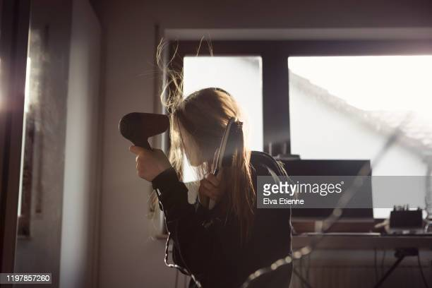 girl (12-13) blow drying her long hair with an electric hairdryer in a bedroom - strom haare stock-fotos und bilder