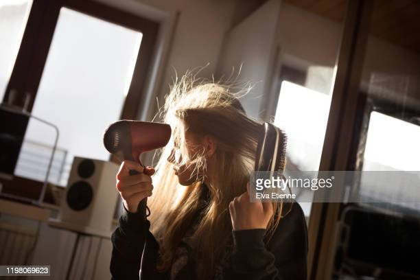 girl (12-13) blow drying her long hair with an electric hairdryer in a bedroom - secador de cabelo - fotografias e filmes do acervo
