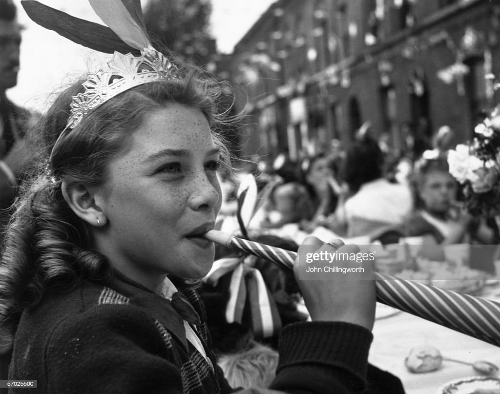 A girl blowing a paper whistle at a party in Morpeth Street in London's East End during Queen Elizabeth II's Coronation celebrations, 2nd June 1953. Original publication: Picture Post - 6542 - Cockneys' Own Party - pub. 1953