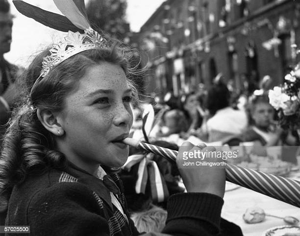 A girl blowing a paper whistle at a party in Morpeth Street in London's East End during Queen Elizabeth II's Coronation celebrations 2nd June 1953...