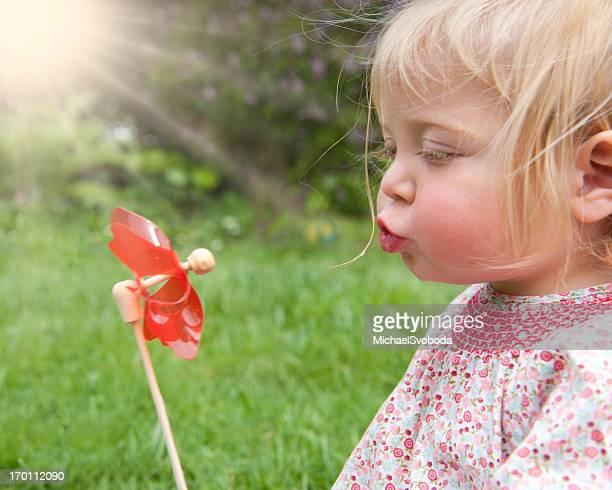 Mädchen Blasen ein Windrad