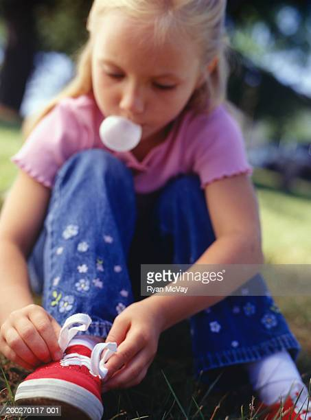 Girl (4-5) blowing bubble and tying tennis shoes, close-up