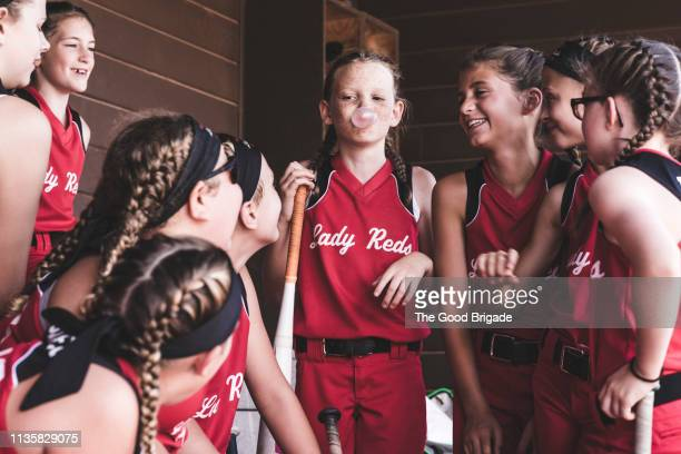 girl blowing bubble gum in dugout during softball game - sports dugout stock pictures, royalty-free photos & images