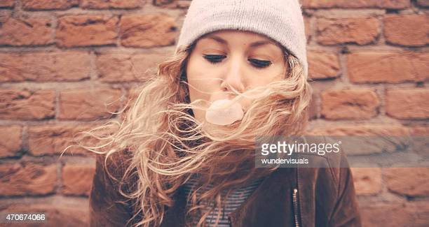Girl blowing bubble gum with a brick wall behind her