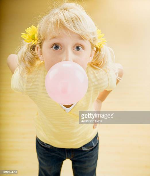 Girl (6-8) blowing bubble with gum