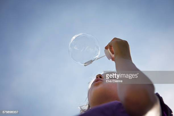 Girl blowing bubbles against sky
