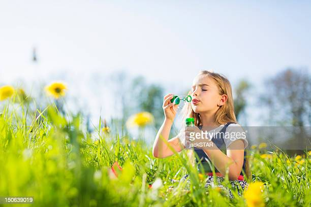 Girl blowing bubbles in field