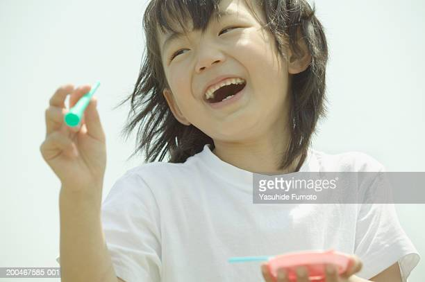 Girl (7-9) blowing bubbles, laughing