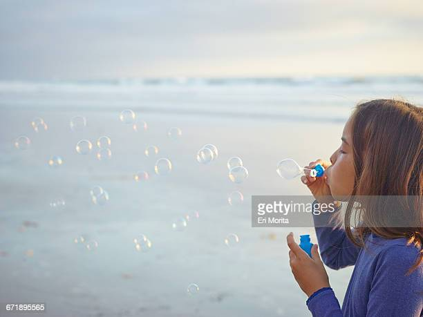 Girl blowing bubbles on beach