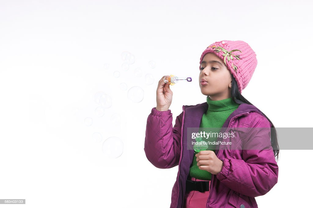 Girl blowing bubbles : Stock Photo