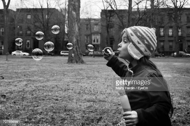 girl blowing bubbles - marty hardin stock photos and pictures