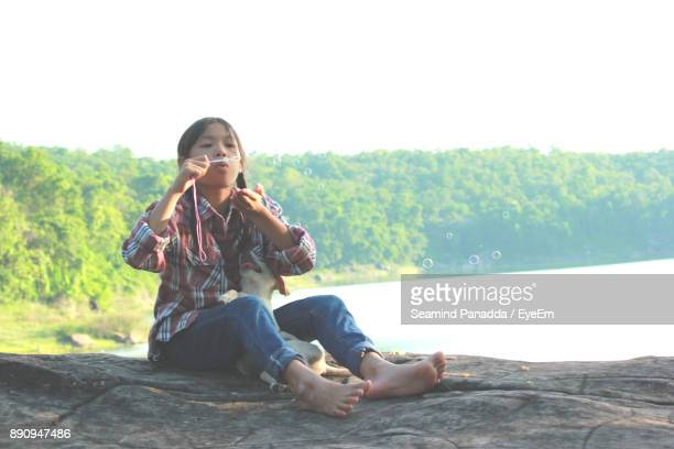 Girl Blowing Bubbles While Sitting On Rock With Puppy