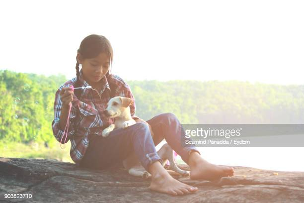 girl blowing bubbles while sitting on rock with puppy - girl blows dog ストックフォトと画像